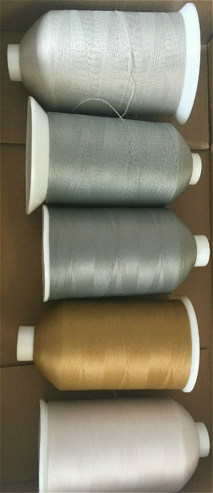 five reels of sewing machine thread in grey beige and white
