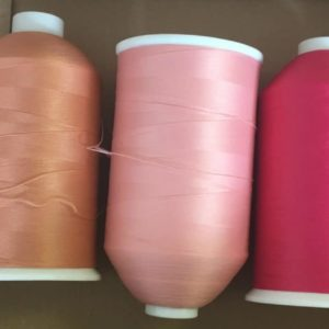 pink sewing machine thread reels