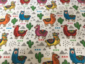 bright multicoloured llama and cactus fabric