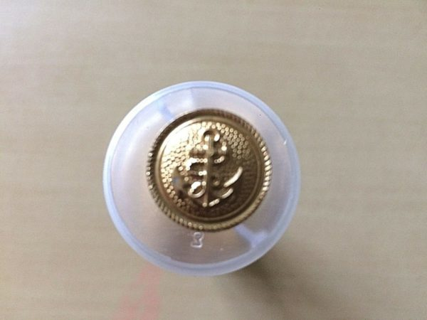 round gold button with anchor design