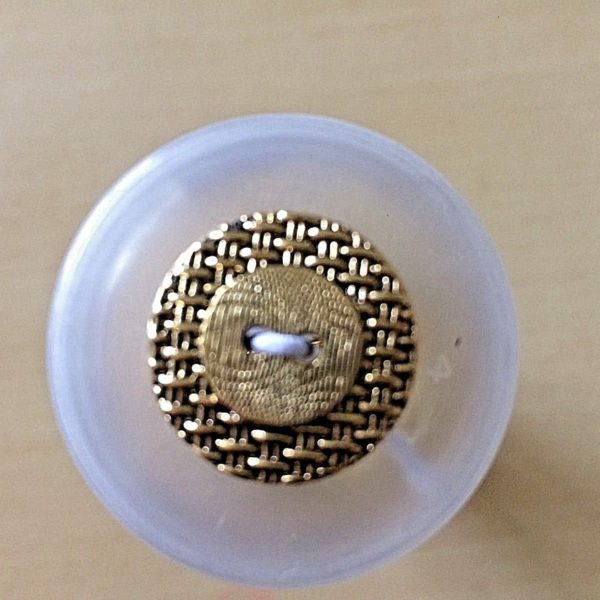 round gold button two holes with criss-cross effect background