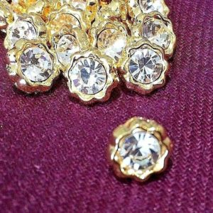 small gold flower button with one white dimante